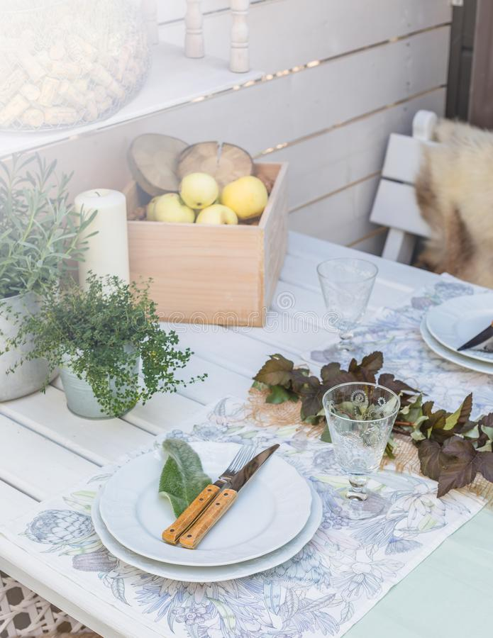 Holiday Summer or early autumn outside table setting with linen napkins and green leaves. Close up. Holiday Summer or early autumn outside table setting with royalty free stock images