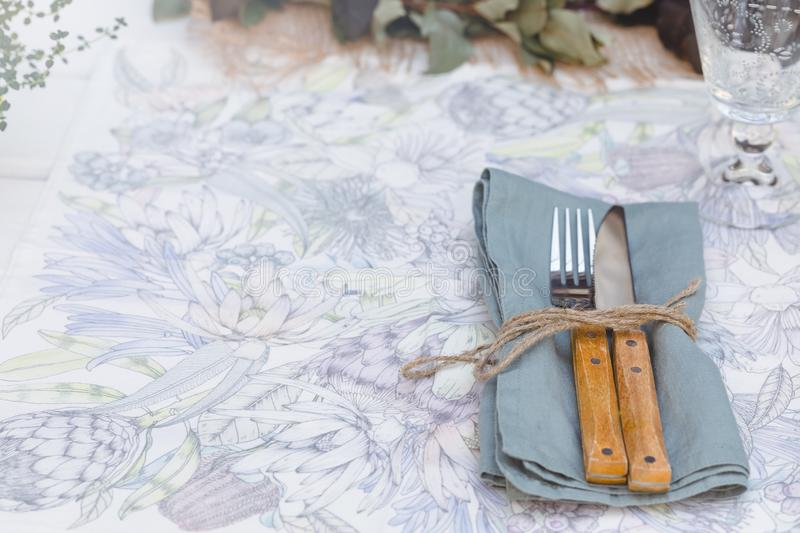Holiday Summer or early autumn outside table setting with linen napkins and green leaves. Close up. Holiday Summer or early autumn outside table setting with stock image