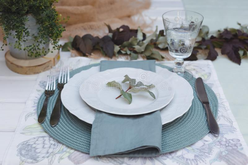 Holiday Summer or early autumn outside table setting with linen napkins and green leaves. Close up. Holiday Summer or early autumn outside table setting with royalty free stock photography