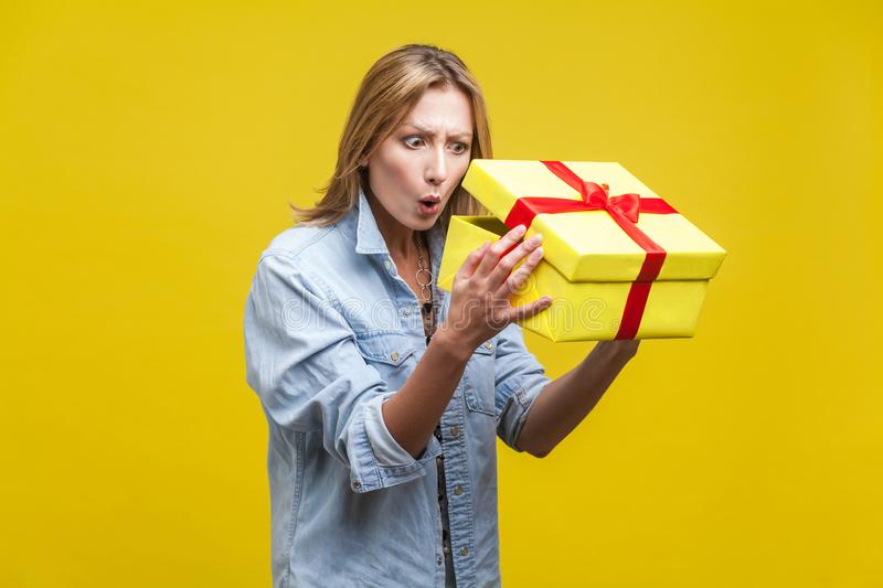 Holiday surprise. Portrait of astonished curious woman in denim shirt looking inside gift box. studio shot  on yellow stock images