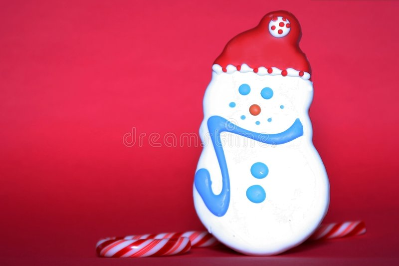 Holiday Sweets Red Background. A snowman cookie and candy cane for the holiday season on a red background royalty free stock photo