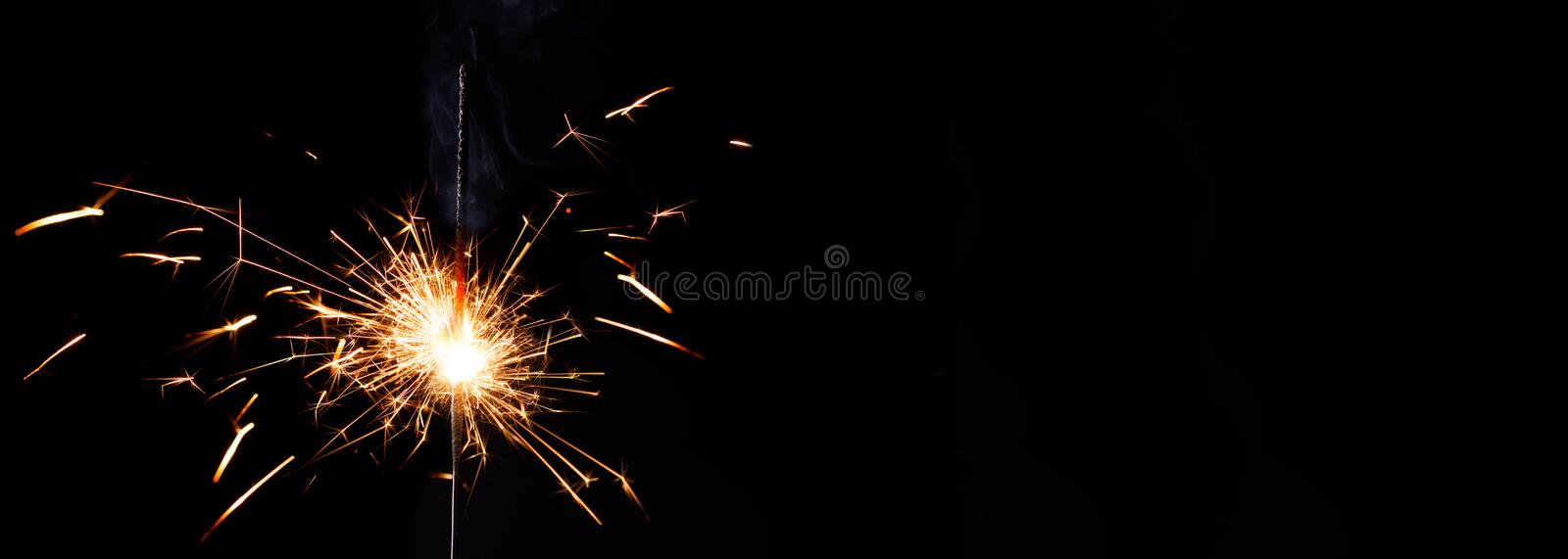 Holiday symbols sparkler on a dark background. Christmas banner. New year party sparkler on black background. Atmosphere of the New Year stock photos