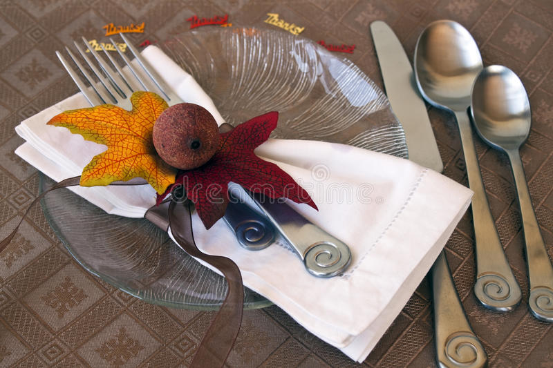 Holiday table setting. With autumn leaves and gourd as a napkin ring. Plate with silverware on a fall place mat royalty free stock photography