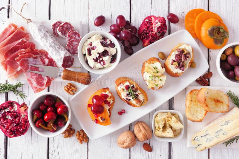 Holiday themed appetizer table spread with assorted cheeses, meats and crostini, above view over white wood stock photo