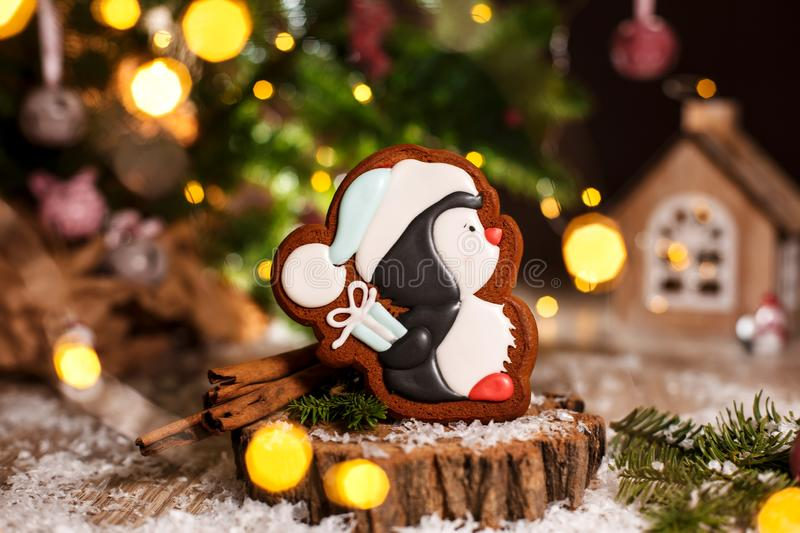 Holiday traditional food bakery. Gingerbread little pinguin in christmas hat with gift in cozy warm decoration with garland lights.  stock image