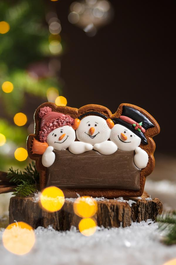 Holiday traditional food bakery. Gingerbread three fun snowmans in cozy warm decoration with garland lights.  royalty free stock images