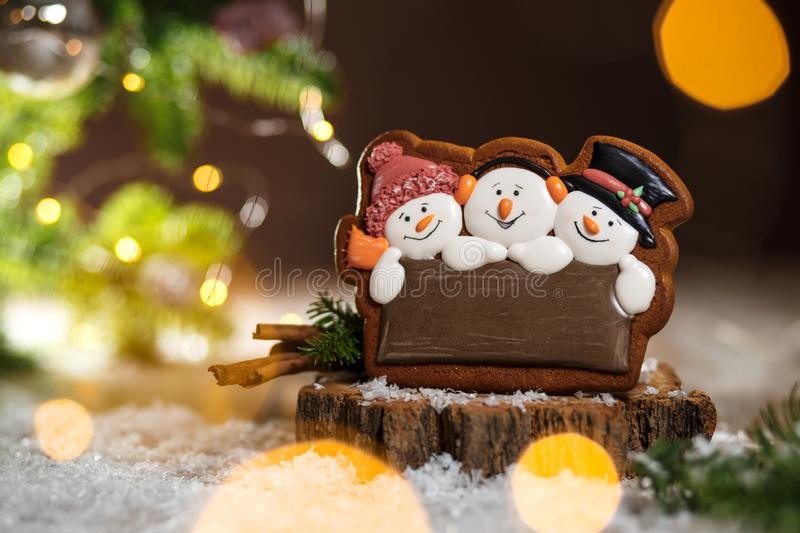 Holiday traditional food bakery. Gingerbread three fun snowmans. In cozy warm decoration with garland lights stock photo