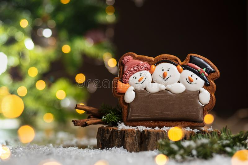 Holiday traditional food bakery. Gingerbread three fun snowmans in cozy warm decoration with garland lights.  stock images
