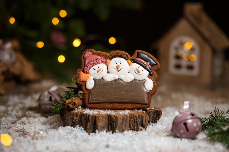 Holiday traditional food bakery. Gingerbread three fun snowmans in cozy warm decoration with garland lights. Holiday traditional food bakery. Gingerbread three stock photo