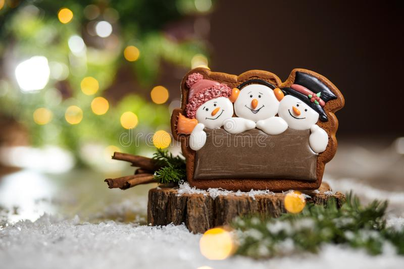 Holiday traditional food bakery. Gingerbread three fun snowmans. In cozy warm decoration with garland lights stock photos