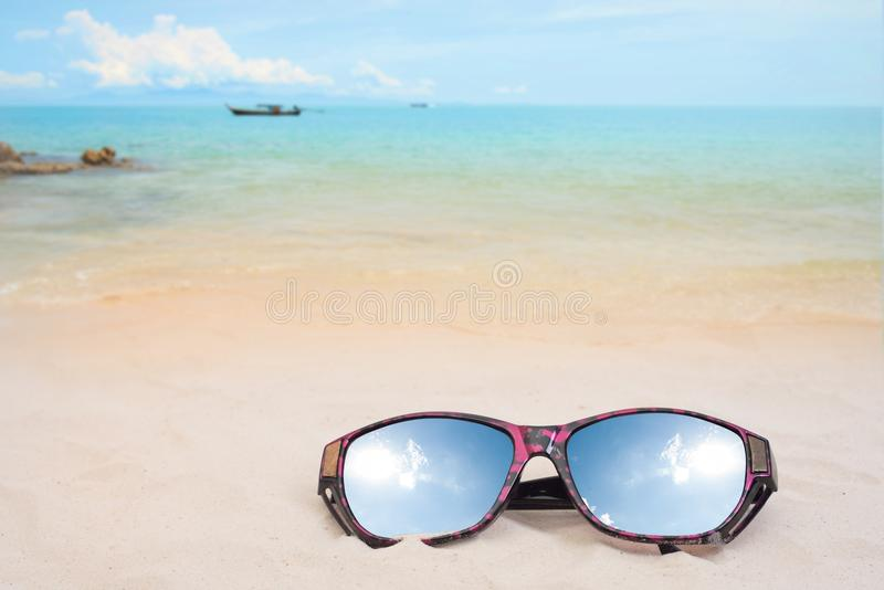 Holiday travel sunglasses on sand beach and sun reflect. Empty space you can place your text or information royalty free stock image