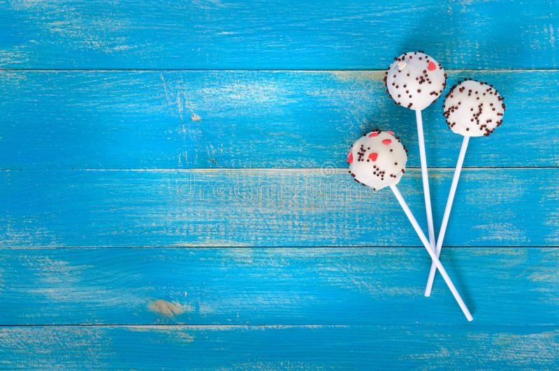 Holiday treats. Cake pops. Biscuit cakes in white chocolate glaze on a bright blue wooden background. royalty free stock images