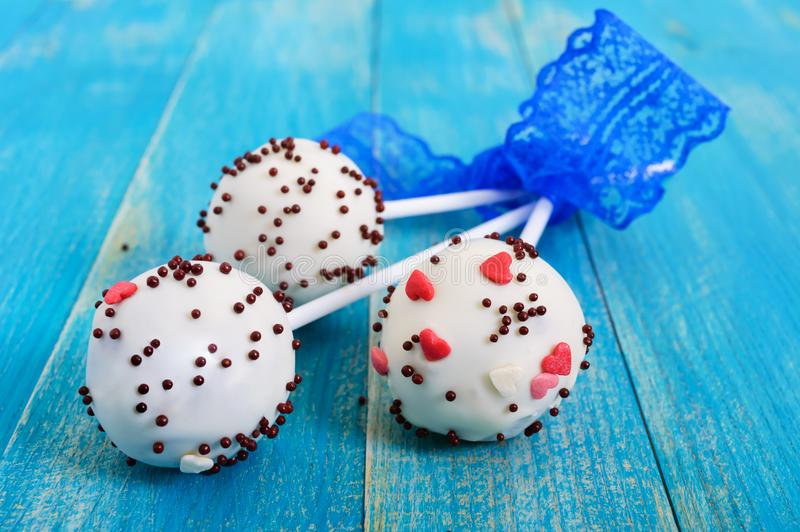 Holiday treats. Cake pops. Biscuit cakes in white chocolate glaze on a bright blue wooden background royalty free stock photos