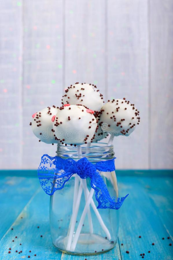 Holiday treats. Cake pops. Biscuit cakes in white chocolate glaze on a bright blue wooden background stock photos