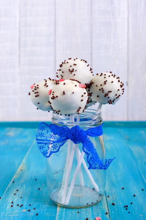 Holiday treats. Cake pops. Biscuit cakes in white chocolate glaze on a bright blue wooden background. royalty free stock photo