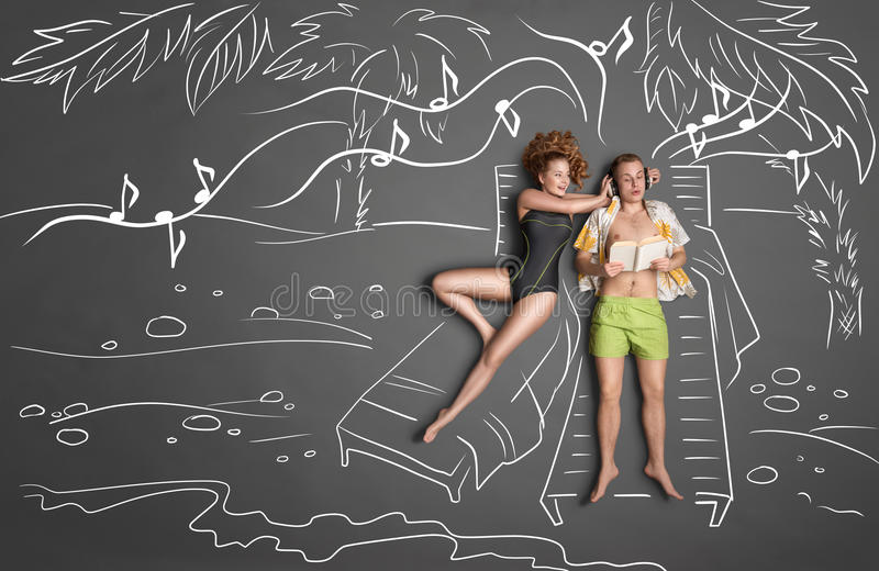 Holiday for two. Love story concept of a romantic couple lying on sun loungers against chalk drawings background. Male listening to the music in the headphones stock illustration