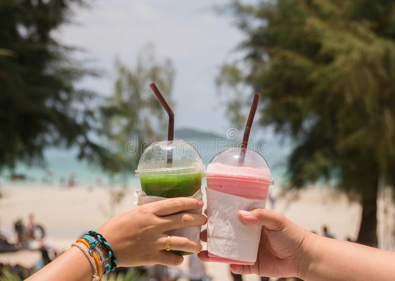 On holiday two women clinking their smoothie on beach in Thailand. royalty free stock photography