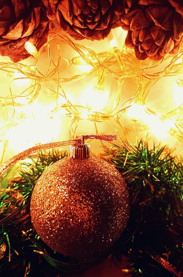 Holiday wallpaper with cones, glitter ball, tinsel and lights. Bright luminous holiday background with golden glitter ball and cedar cones royalty free stock images