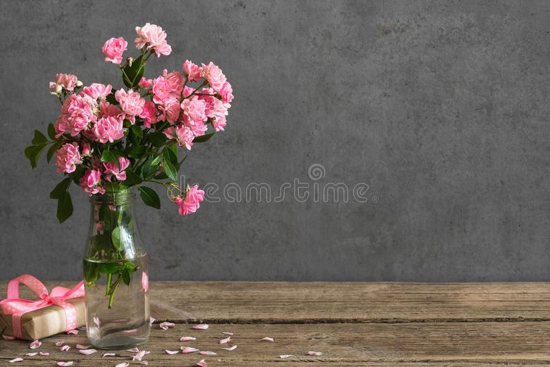 Holiday or wedding card. still life with pink rose flowers bouquet and gift box. spring background stock photo