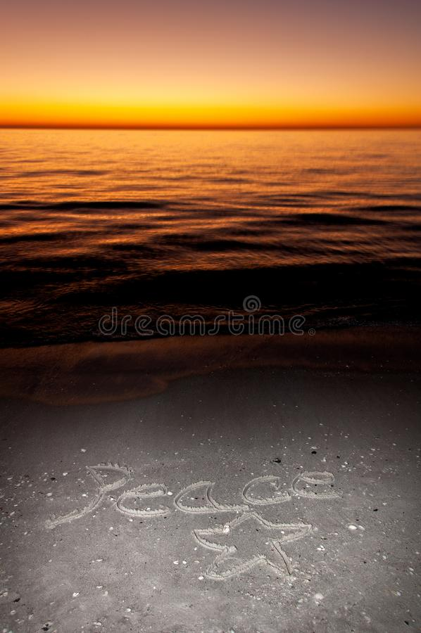 Holiday wishes for Peace written in the sand. Holiday wishes for Peace written in the sand at the beach along the Gulf of Mexico with orange, yellow and pink royalty free stock image