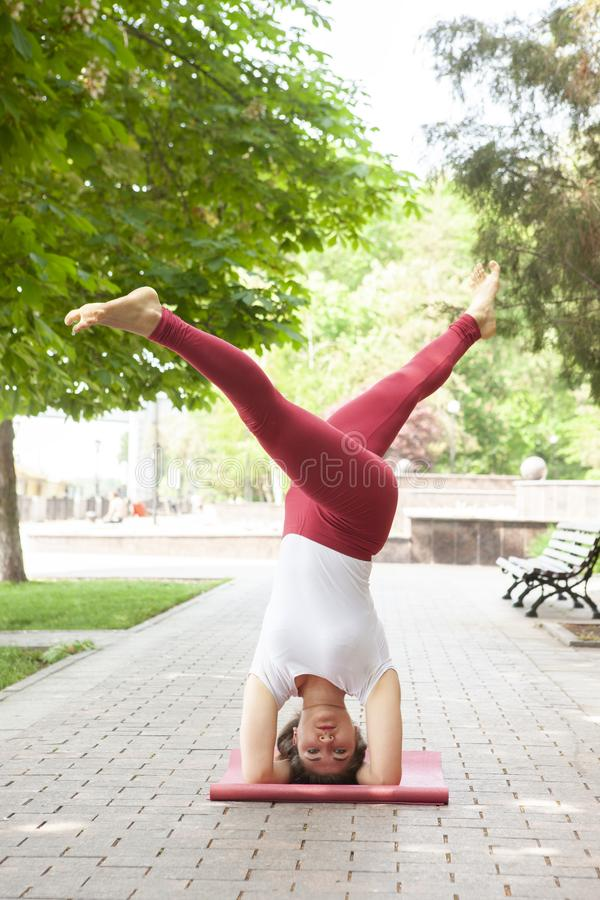 Holiday woman doing yoga pose meditation in the public park Sport Healthy concept. Portrait royalty free stock images