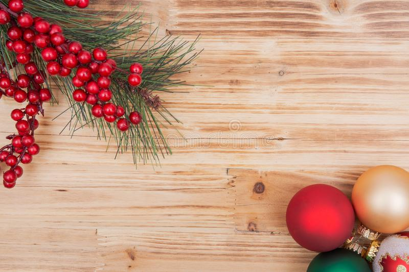 Holiday wooden background with pine and berry bush and ornament Christmas tree balls on wood. En background royalty free stock photography