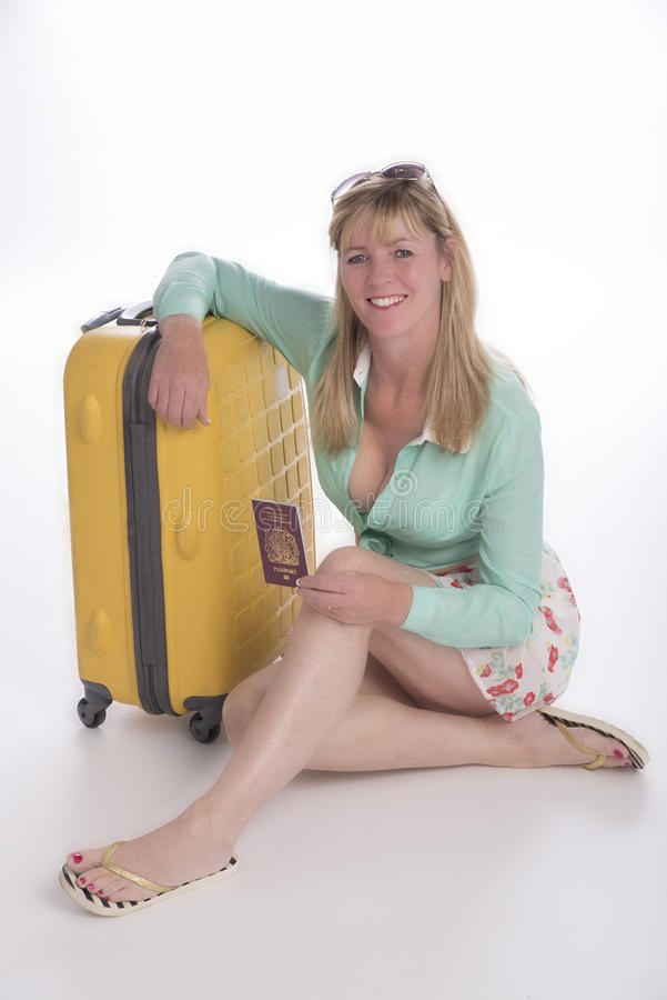 Holidaymaker with passport and luggage. Woman holidaymaker in short summer skirt holding her passport and leaning on a yellow suitcase royalty free stock images
