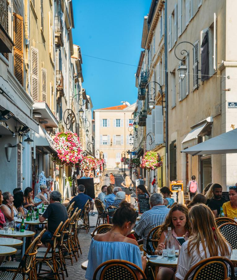 Holidaymakers in Antibes, Cote d`Azur, France sit at a terrace in a restaurant during the summer. Antibes, France - July 8th, 2018: Holidaymakers in Antibes royalty free stock photos