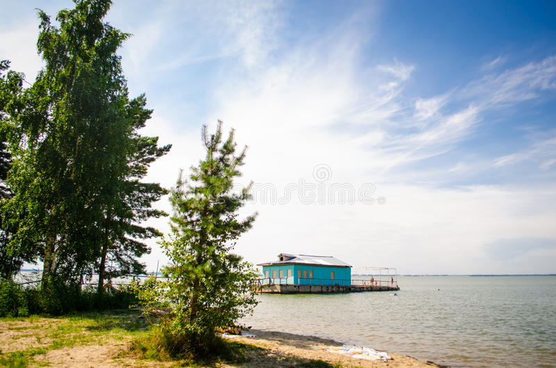 Holidaymakers sunbathe and swim at the beach at the old pier.  royalty free stock photos