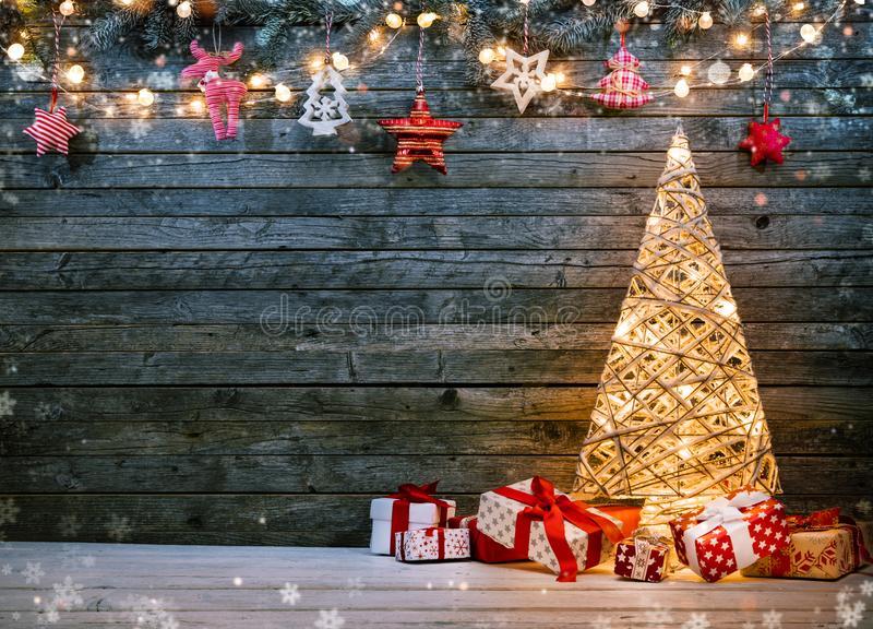 Holidays background with illuminated Christmas tree, gifts and d. Ecoration. Dark wooden background with free space for text. Celebration of christmas stock photo