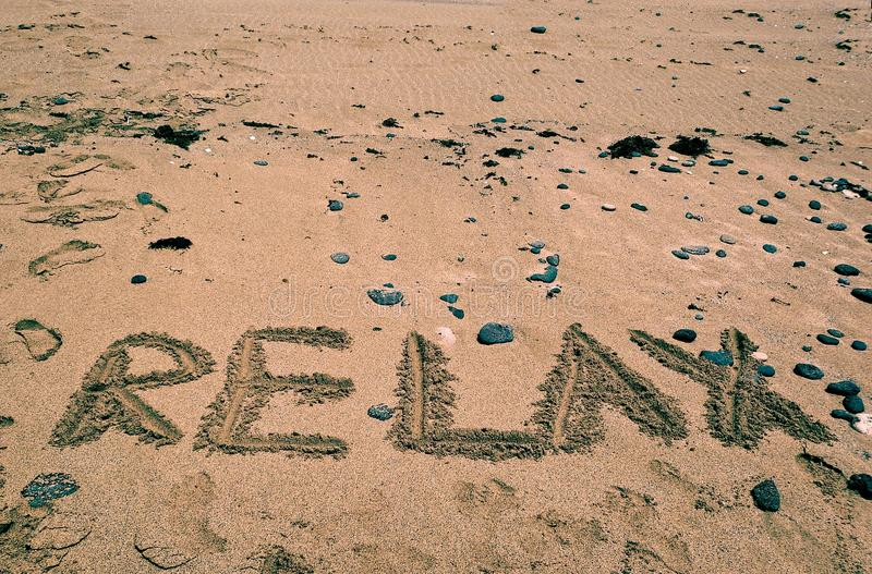 Holidays background with RELAX word written on sandy beach. Holidays background. Summer. In relax mood royalty free stock photo