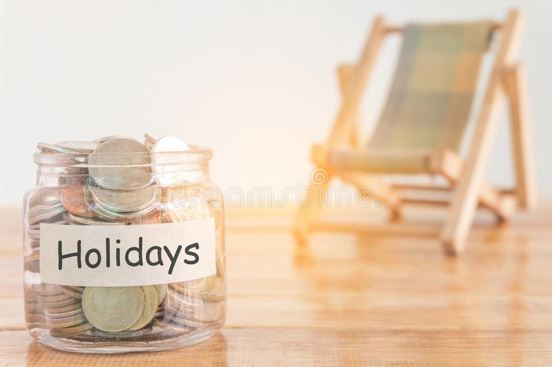 Holidays budget concept. Holidays money savings concept. Collecting money in the money jar for Holidays. Money jar with coins and. stock photos