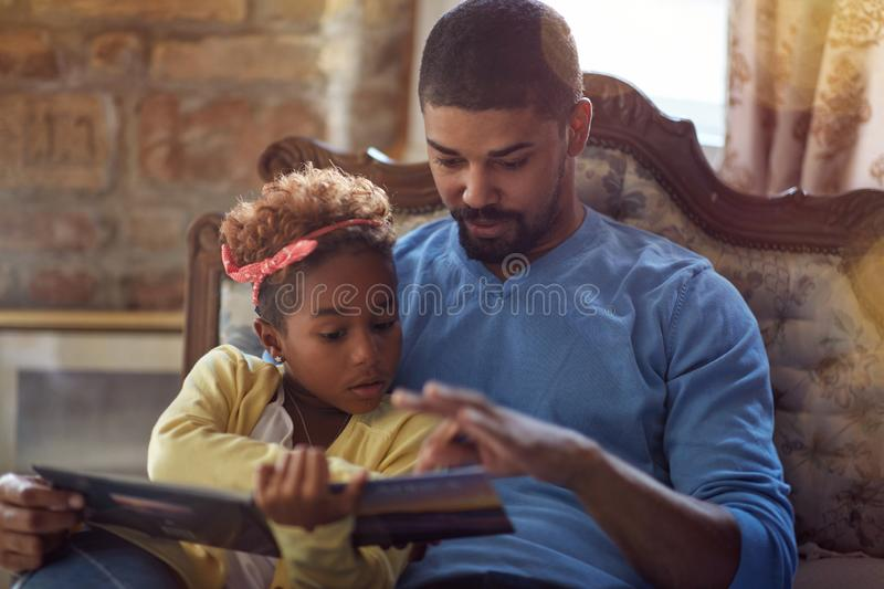 Holidays and celebration concept - Father and daughter reading Christmas fairy tales stock photo