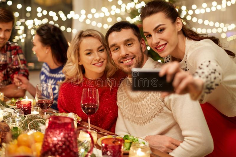 Friends having christmas dinner and taking selfie royalty free stock photo