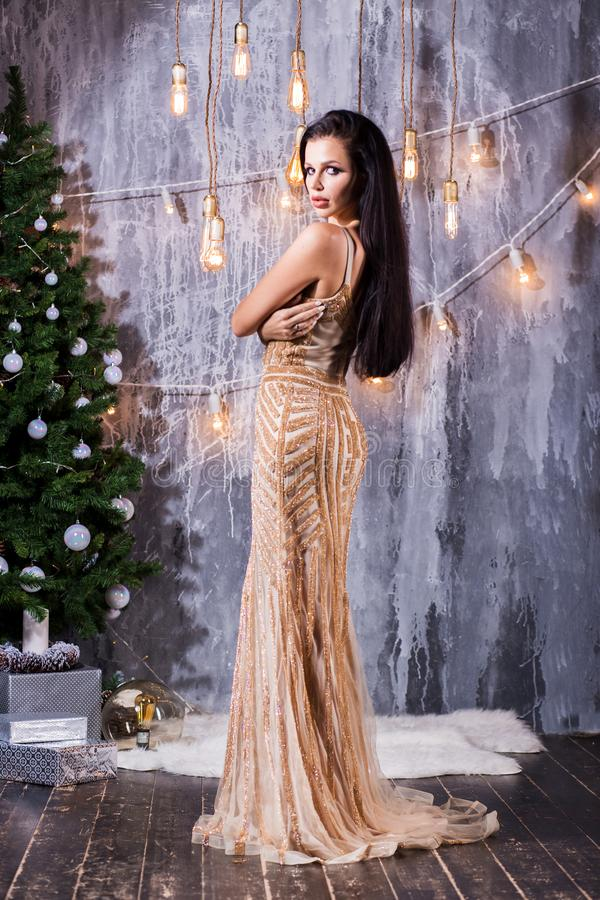 Holidays, celebration and people concept - young brunette woman in elegant Golden long dress over christmas interior background. Holidays, New Year royalty free stock photos