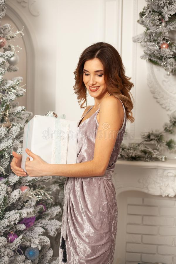 Holidays, celebration and people concept - young smiling woman in elegant violet dress over christmas interior background royalty free stock photos