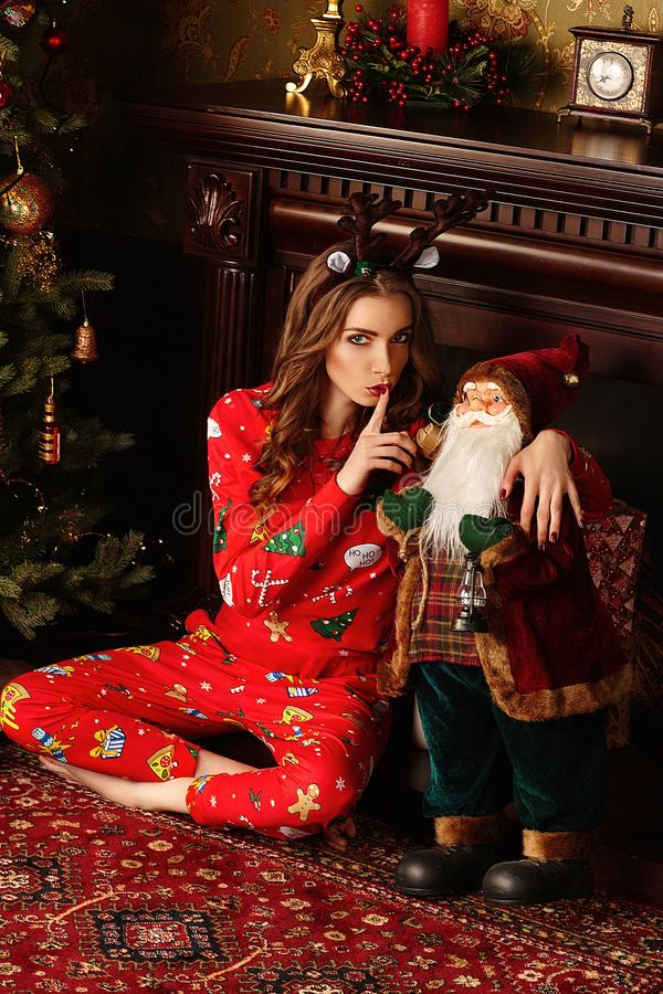 Holidays, celebration and people concept - young woman brunette curly hair , dressed in a Christmas suit over Christmas interior b stock photography