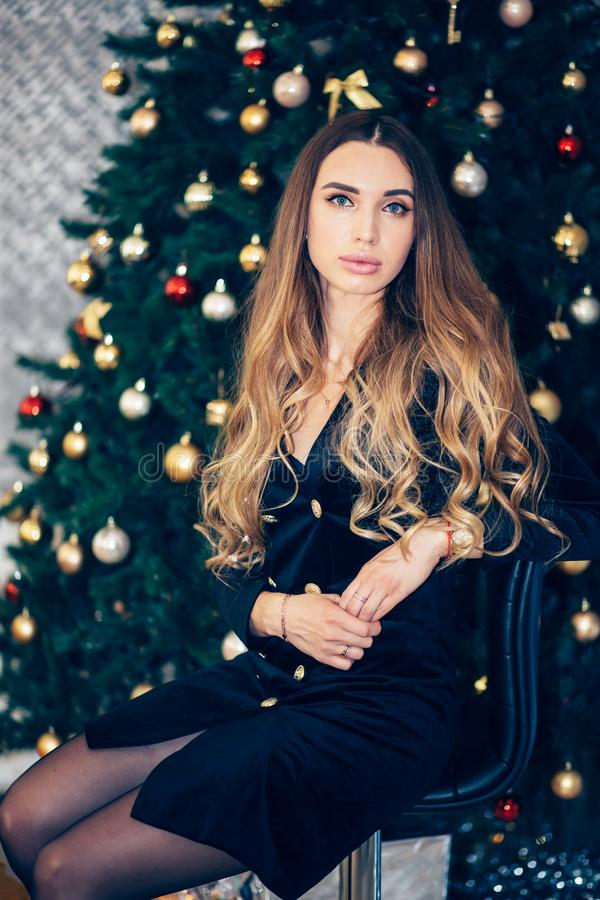 Holidays, celebration and people concept - young woman in elegant dress over christmas interior background. Girl in black dress ne stock photo