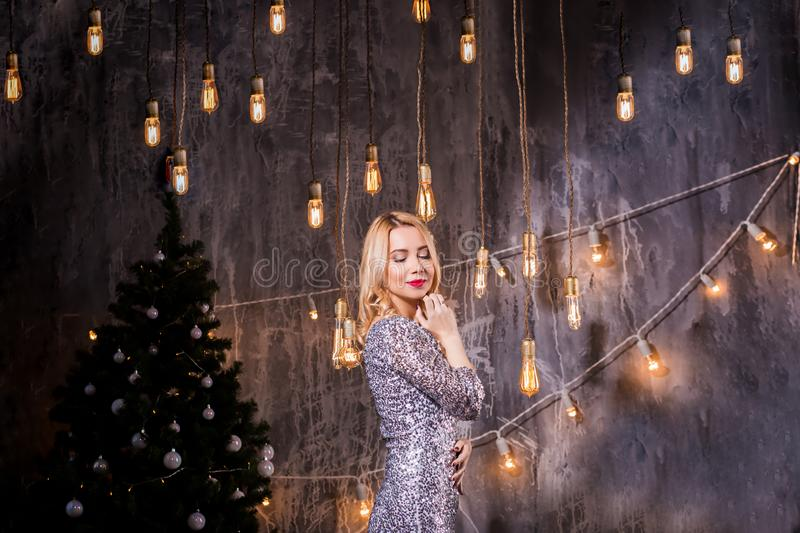 Holidays, celebration and people concept - young woman in elegant dress over christmas interior background. Young beautiful blonde. Girl smiling, eyes closed stock image