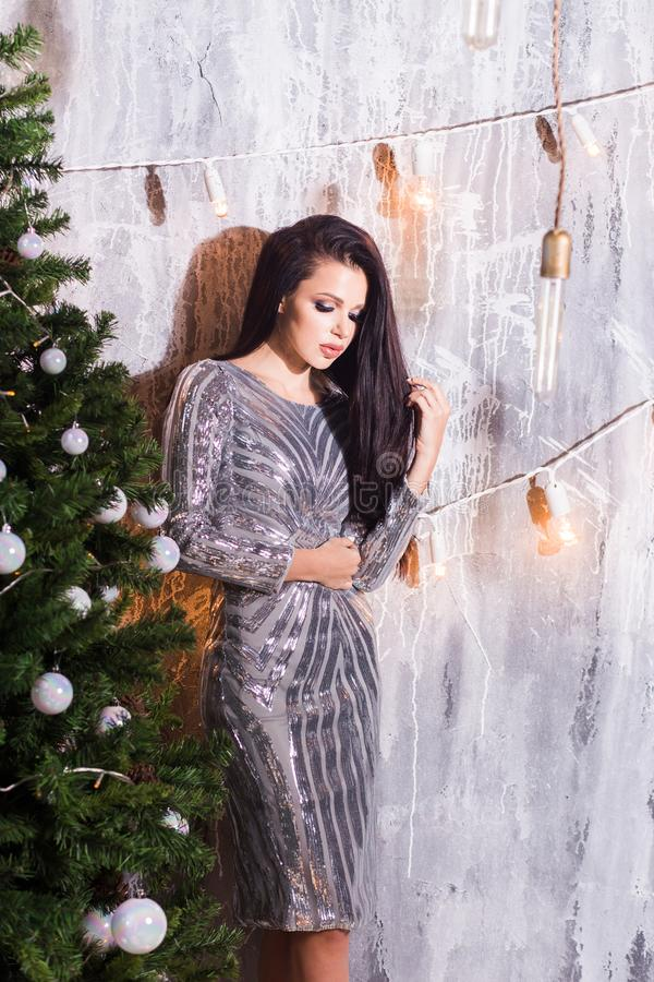 Holidays, celebration and people concept - young woman in elegant dress over christmas interior. Background stock photo