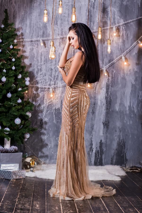 Holidays, celebration and people concept - young woman in elegant Golden long dress over christmas interior background. Image with. Happy young woman in elegant stock image
