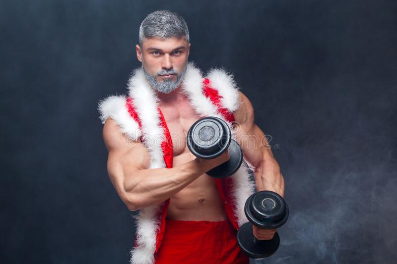 Holidays and celebrations, New year, Christmas, sports, bodybuilding, healthy lifestyle - Muscular handsome Santa. Claus. on a black background with dumbbells stock photo