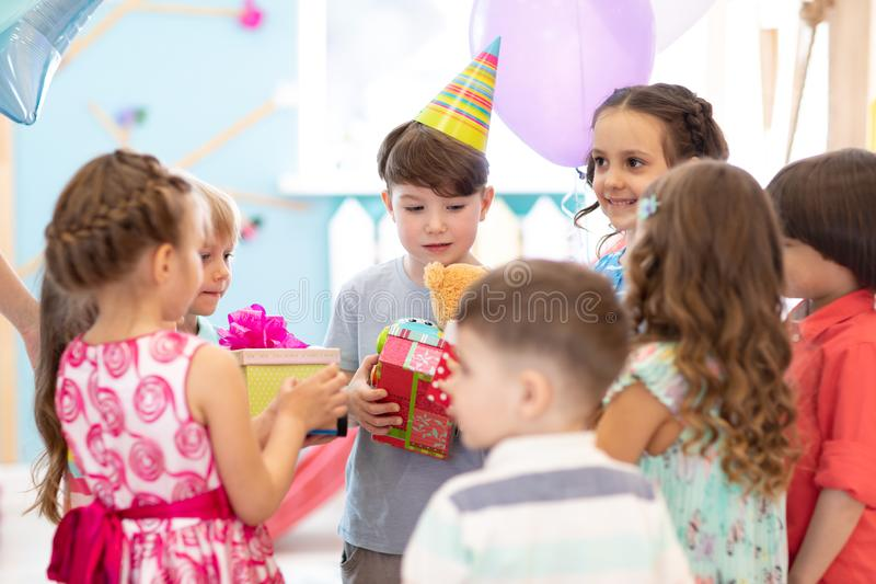 Holidays, childhood and celebration concept - happy friends giving presents to birthday child at party in daycare. Holidays, childhood and celebration concept stock photography