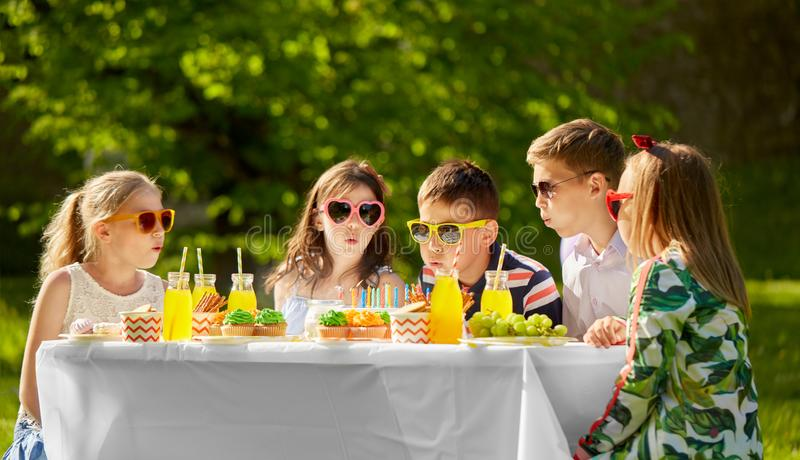 Happy kids on birthday party at summer garden. Holidays, childhood and celebration concept - happy kids blowing out candles on birthday cake sitting at table at royalty free stock photo