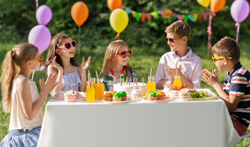 Happy kids with cake on birthday party at summer. Holidays, childhood and celebration concept - happy kids with candles on cake sitting at table at summer garden royalty free stock photo