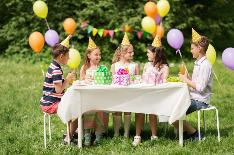 Happy kids on birthday party at summer garden. Holidays, childhood and celebration concept - happy kids sitting at table on birthday party at summer garden stock photo