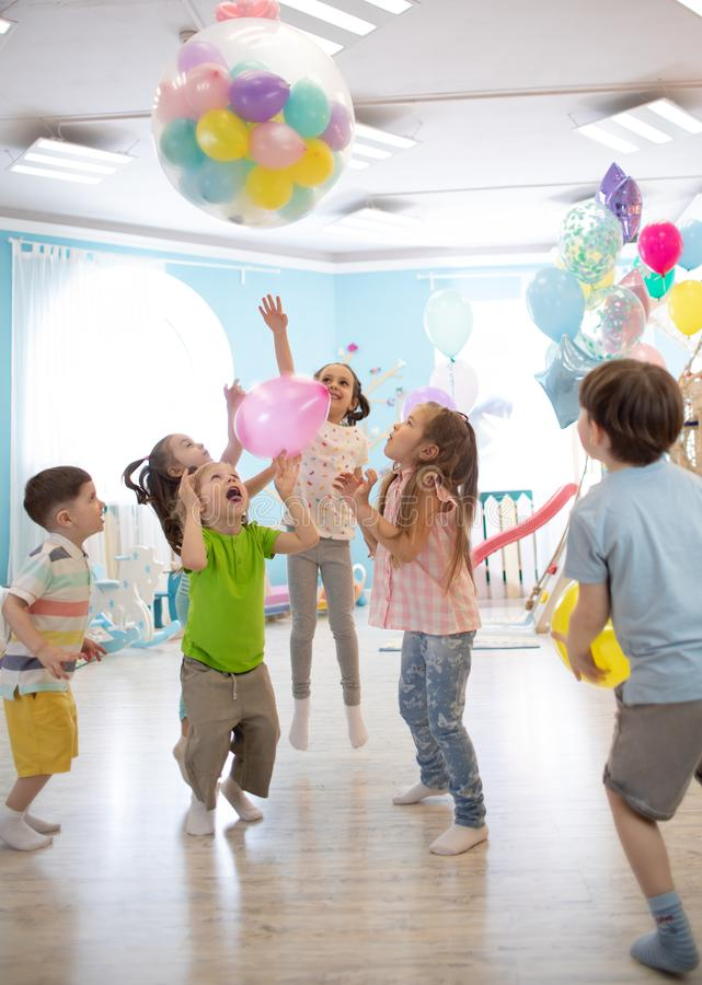 Holidays, childhood and celebration concept - several kids having fun and jumping on birthday party in entertainment royalty free stock images
