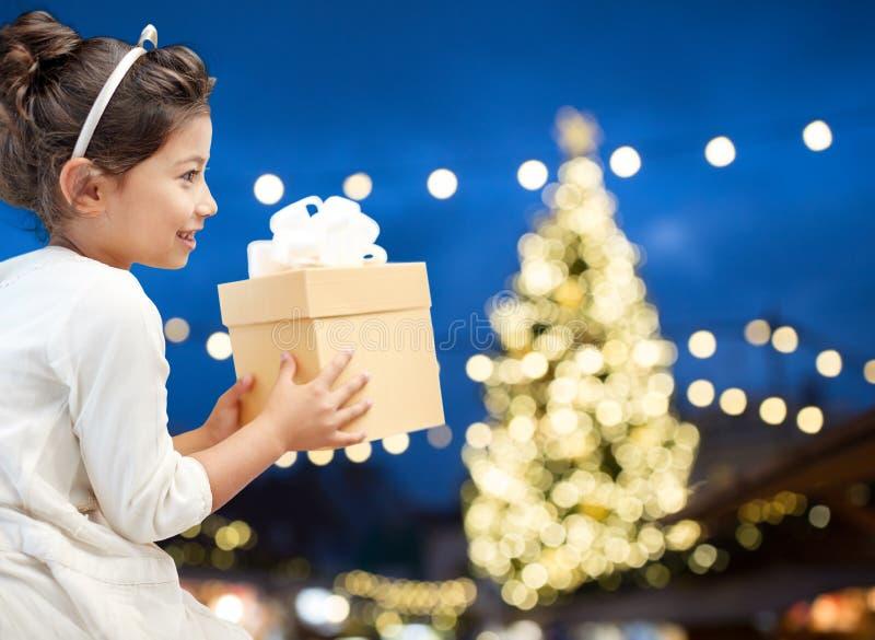 Happy girl with gift box over christmas lights stock photos