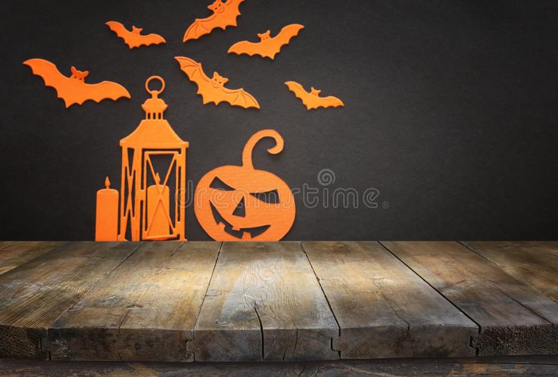 Holidays concept of Halloween. Empty rustic table in front of bats, pumpkin and lantern background. Ready for product display stock images