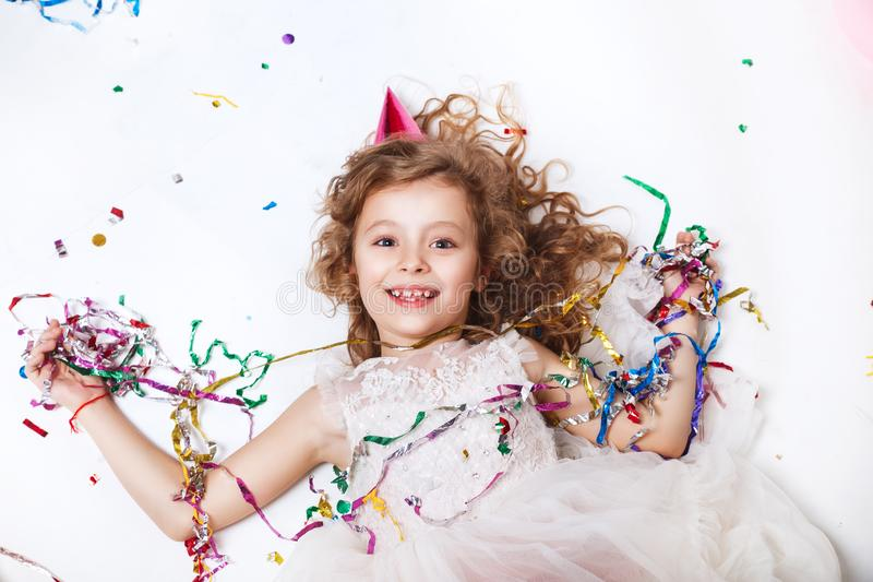 Holidays concept. Little funny girl lying in multicolored confetti on birthday party. Funny happy girl celebrating birthday party, smiling and lying in stock image